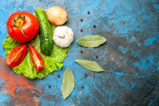 Vista superior de pepino de verduras frescas con ensalada de tomate y ajo sobre fondo azul.