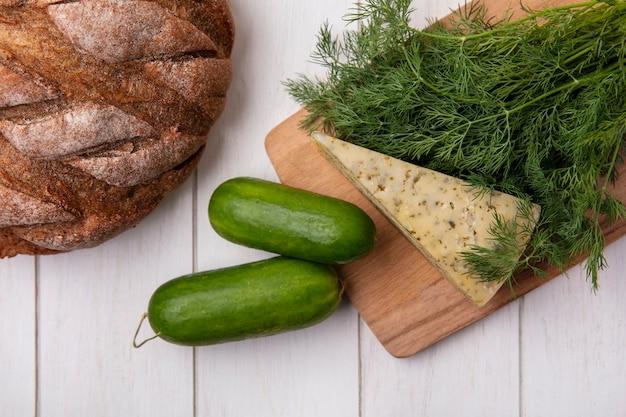 Vista superior de pepinos con una hogaza de pan negro con queso y eneldo sobre un fondo blanco.