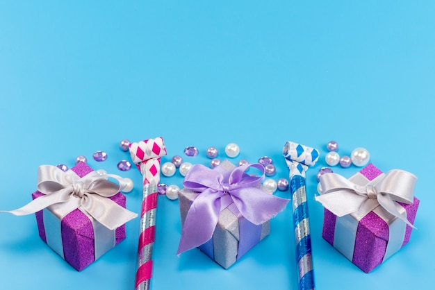 Una vista superior de pequeñas cajas púrpuras para cumpleaños aislado en azul, fiesta de celebración de cumpleaños