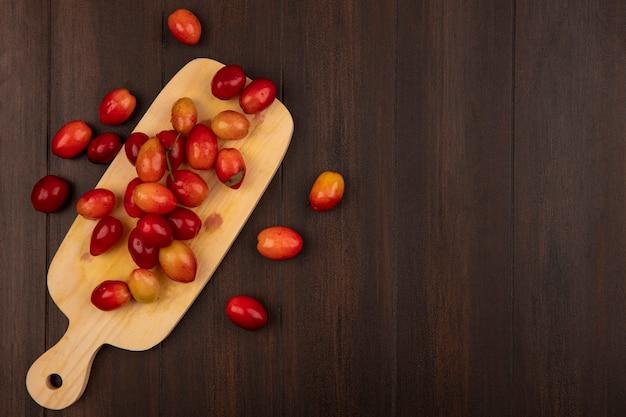 Vista superior de pequeñas cerezas de cornalina agridulce sobre una tabla de cocina de madera sobre una superficie de madera con espacio de copia