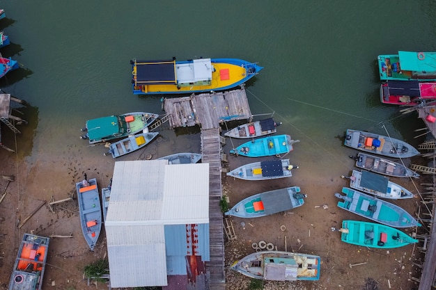 Vista superior de las pequeñas embarcaciones en la orilla del lago y un viejo muelle de madera