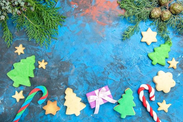Vista superior de pequeñas figuras de árboles con regalos sobre una superficie azul