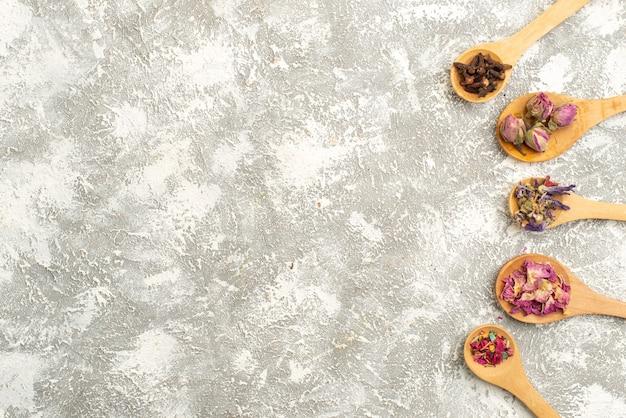 Vista superior de pequeñas flores secas en cucharas de madera sobre fondo blanco polvo de árbol de planta de flor