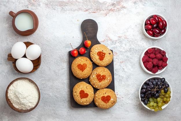 Vista superior de pequeñas galletas de azúcar deliciosos dulces para té con bayas en superficie blanca pastel de galleta de azúcar galleta pastel dulce