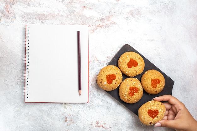 Vista superior de pequeñas galletas de azúcar deliciosos dulces para el té con el bloc de notas en la superficie blanca pastel galleta azúcar galleta pastel