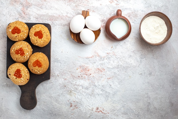 Vista superior pequeñas galletas de azúcar deliciosos dulces para té con huevos y leche en el escritorio blanco pastel de galletas de azúcar galleta pastel dulce