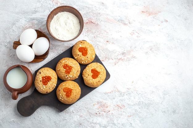 Vista superior pequeñas galletas de azúcar deliciosos dulces para té con huevos y leche en la superficie blanca pastel galleta azúcar galleta pastel dulce