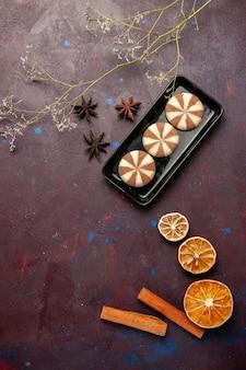 Vista superior pequeñas galletas con canela en superficie oscura
