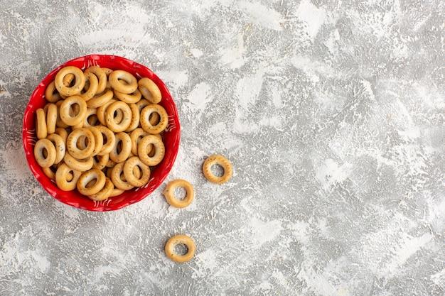 Vista superior pequeñas galletas dentro de la placa sobre la superficie blanca
