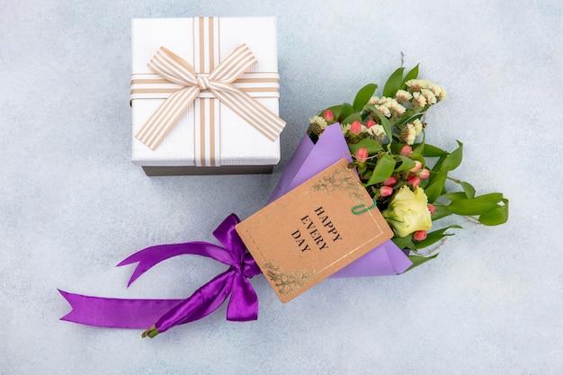 Vista superior de pequeñas y maravillosas flores y caja de regalo sobre superficie blanca