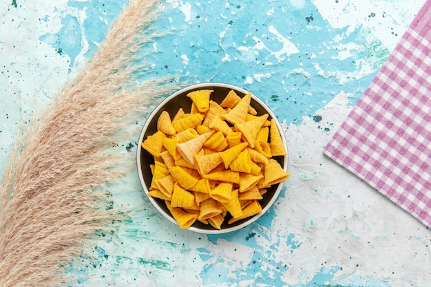 Vista superior pequeñas patatas fritas picantes dentro de la placa sobre fondo azul claro patatas fritas de color crujiente calorías