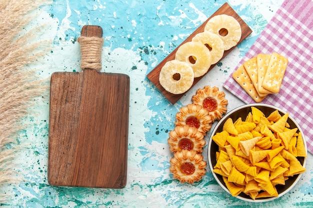 Vista superior pequeñas patatas fritas picantes con galletas, anillos de piña secos y galletas sobre fondo azul claro, patatas fritas de color, calorías crujientes.