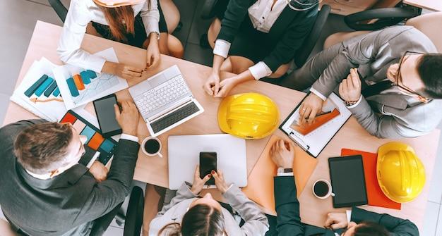 Vista superior del pequeño grupo de arquitectos en ropa formal sentados a la mesa y haciendo el proyecto. sea terco con los objetivos y flexible con sus métodos.