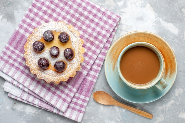 Vista superior pequeño pastel de cerezas azúcar en polvo con café con leche en el fondo gris pastel de azúcar galleta dulce