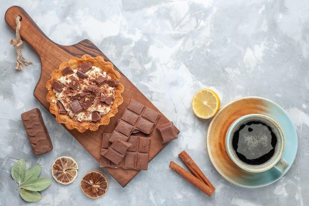 Vista superior de un pequeño pastel de crema con barras de chocolate y té en la mesa de luz, pastel dulce, crema de azúcar, chocolate