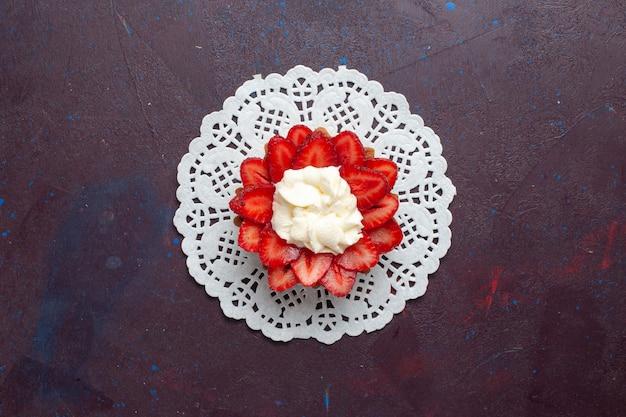 Vista superior del pequeño pastel cremoso con frutas en rodajas sobre la superficie oscura
