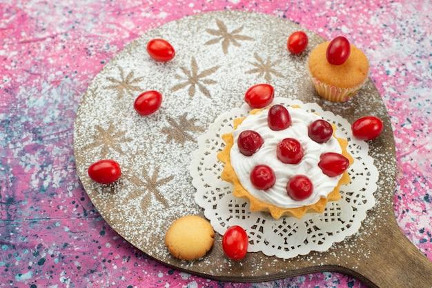 Vista superior pequeño pastel cremoso con frutos rojos en la superficie púrpura dulce de azúcar