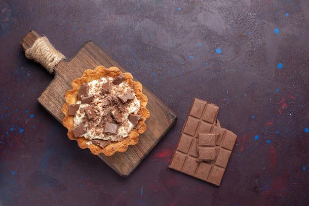 Vista superior del pequeño pastel cremoso con trozos de chocolate y barras en superficie oscura