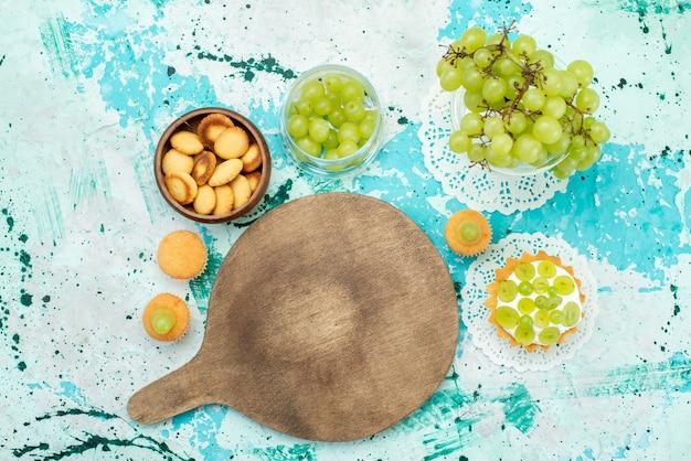 Vista superior del pequeño pastel con deliciosa crema y galletas de uvas verdes frescas y en rodajas aisladas en azul, pastel de fruta dulce azúcar hornear