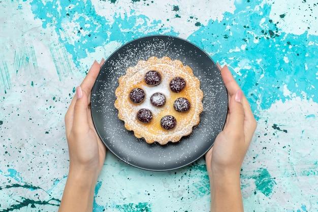 Vista superior pequeño pastel delicioso con azúcar en polvo y frutas dentro de la placa en la mesa azul claro pastel de frutas dulce hornear