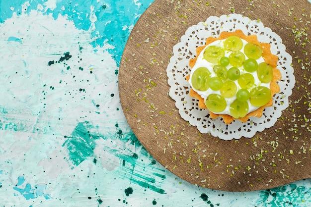 Vista superior pequeño pastel delicioso con deliciosa crema y uvas en rodajas en el fondo azul claro pastel dulce azúcar fruta