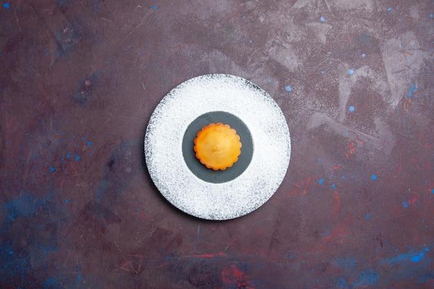 Vista superior pequeño pastel delicioso dentro de la placa en la superficie oscura pastel dulce galleta galleta pastel de té
