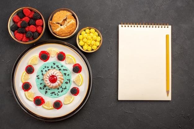 Vista superior pequeño pastel delicioso con rodajas de limón y caramelos en el fondo oscuro pastel de galletas fruta cítrica galleta dulce