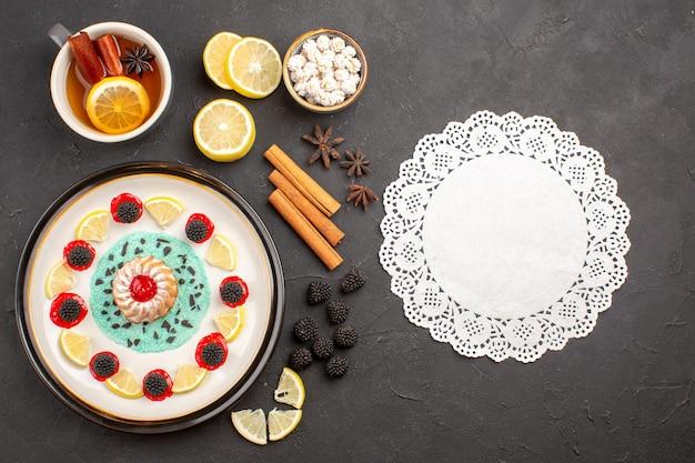 Vista superior del pequeño pastel delicioso con rodajas de limón y una taza de té sobre fondo oscuro, frutas cítricas, galletas, galletas, dulces.