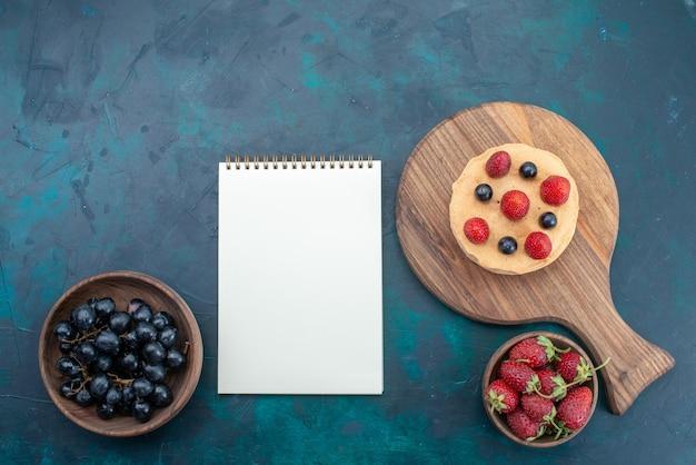 Vista superior del pequeño pastel con fresas frescas en la superficie azul oscuro