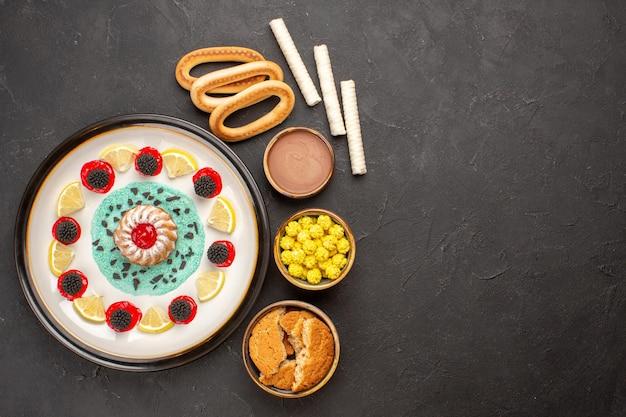 Vista superior pequeño pastel de galletas con rodajas de limón y caramelos en el fondo oscuro pastel galleta dulce fruta cítrica galleta