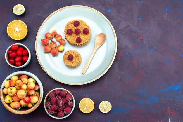Vista superior del pequeño pastel redondo con frambuesas frescas dentro de la placa con frutas frescas sobre una superficie oscura