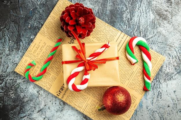 Vista superior pequeño regalo atado con caramelos de navidad de cinta roja en periódico sobre superficie gris