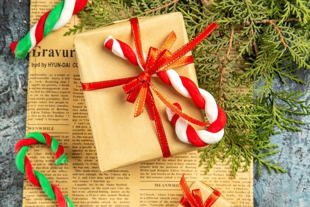 Vista superior pequeño regalo atado con cinta roja caramelos de navidad en ramas de pino de periódico sobre superficie gris