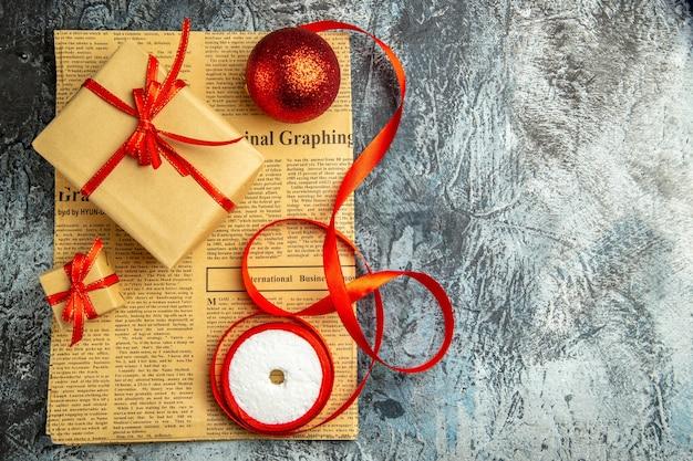 Vista superior pequeño regalo atado con cinta roja cinta de bola roja en periódico sobre superficie oscura