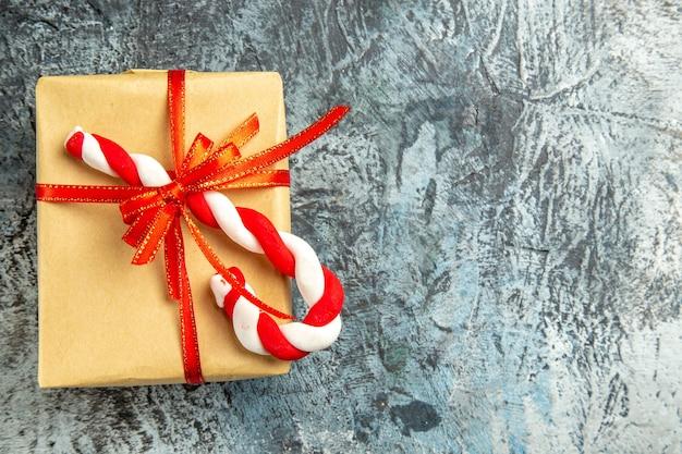 Vista superior pequeño regalo atado con cinta roja dulces de navidad en el espacio de copia de fondo gris
