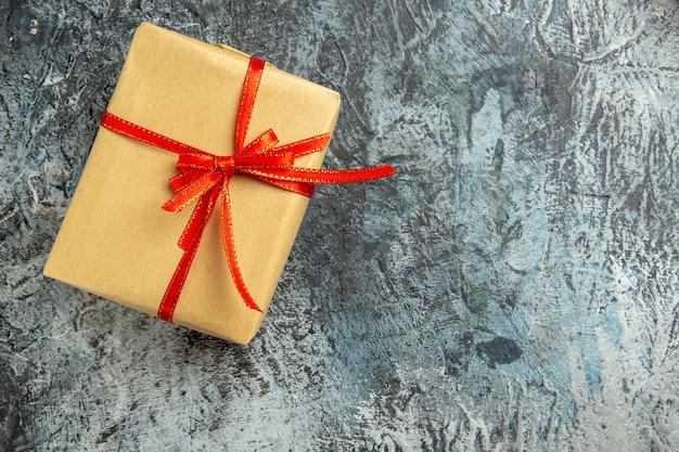 Vista superior pequeño regalo atado con cinta roja sobre superficie oscura