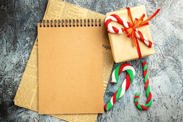 Vista superior pequeño regalo atado con cuaderno de cinta roja en caramelos de navidad de periódico en superficie gris