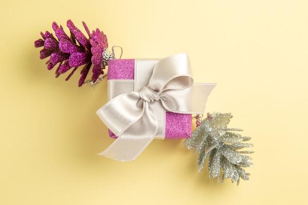 Vista superior del pequeño regalo de navidad en la superficie de color amarillo claro