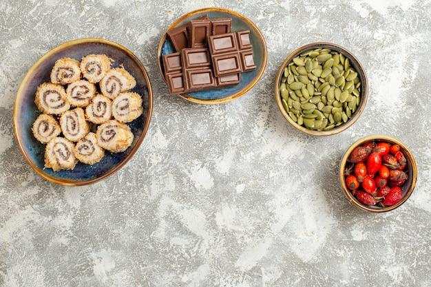 Vista superior de pequeños caramelos de rollo con barras de chocolate sobre fondo blanco.