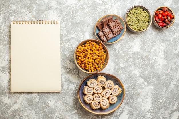 Vista superior de pequeños caramelos de rollo con chocolate sobre fondo blanco claro