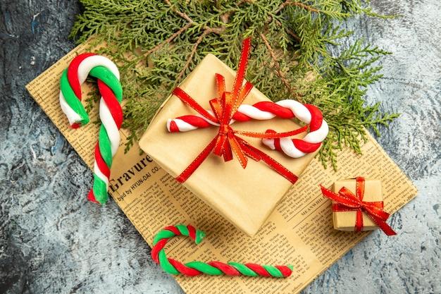 Vista superior pequeños obsequios atados con dulces de navidad de cinta roja en periódico sobre superficie gris