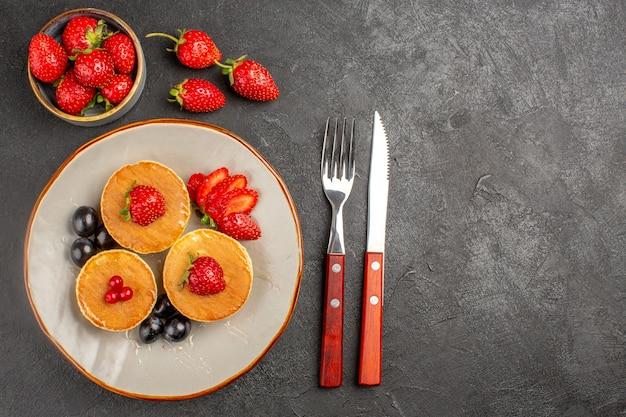 Vista superior pequeños panqueques deliciosos con frutas en la superficie de color gris oscuro pastel pastel de frutas