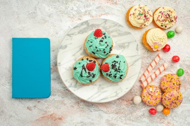 Vista superior de pequeños pasteles de crema con caramelos de colores y galletas en la superficie blanca golosinas pastel de color de postre de caramelo de arco iris