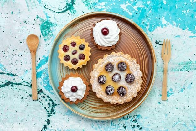 Vista superior de pequeños pasteles con crema de fruta de azúcar en polvo dentro de la placa en la mesa azul claro pastel crema fruta dulce
