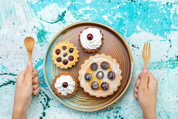 Vista superior de pequeños pasteles con crema de frutas de azúcar en polvo en mesa de luz pastel crema té de frutas