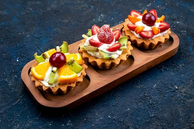 Una vista superior de pequeños pasteles con crema y frutas frescas en rodajas en el azúcar de pastel de frutas de fondo azul