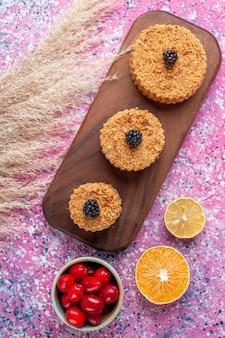 Vista superior de pequeños pasteles deliciosos con cornejos sobre superficie rosa claro