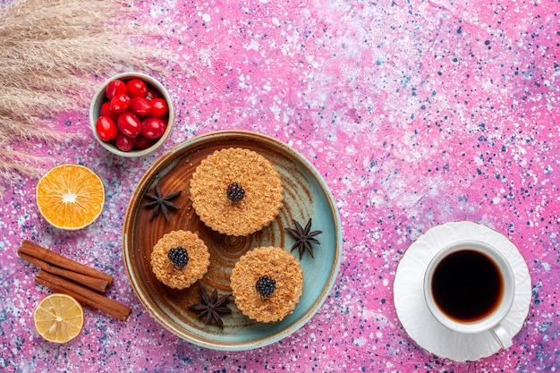 Vista superior de pequeños pasteles deliciosos con cornejos y té en la superficie de color rosa claro
