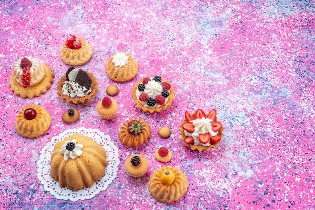 Vista superior pequeños pasteles deliciosos con crema junto con diferentes bayas en el fondo claro pastel baya dulce hornear