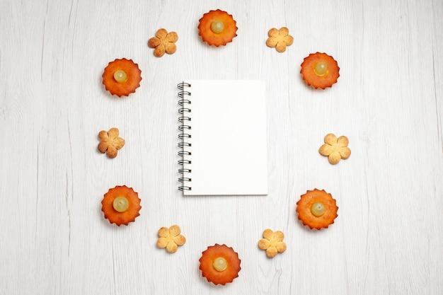 Vista superior pequeños pasteles deliciosos forrados con galletas en la superficie blanca postre galleta pastel de té pastel galleta dulce